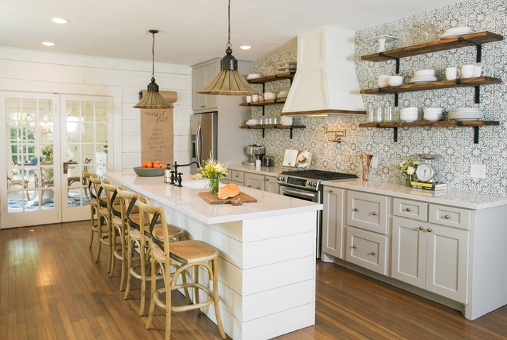 The kitchen of the newly renovated Childers home has been completely transformed, a wall was removed to open the space, a custom island installed, and stainless steel appliances were added, as seen on Fixer Upper. (after)