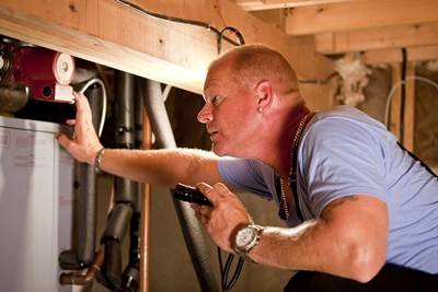 Mike Holmes looking at a home's pipes