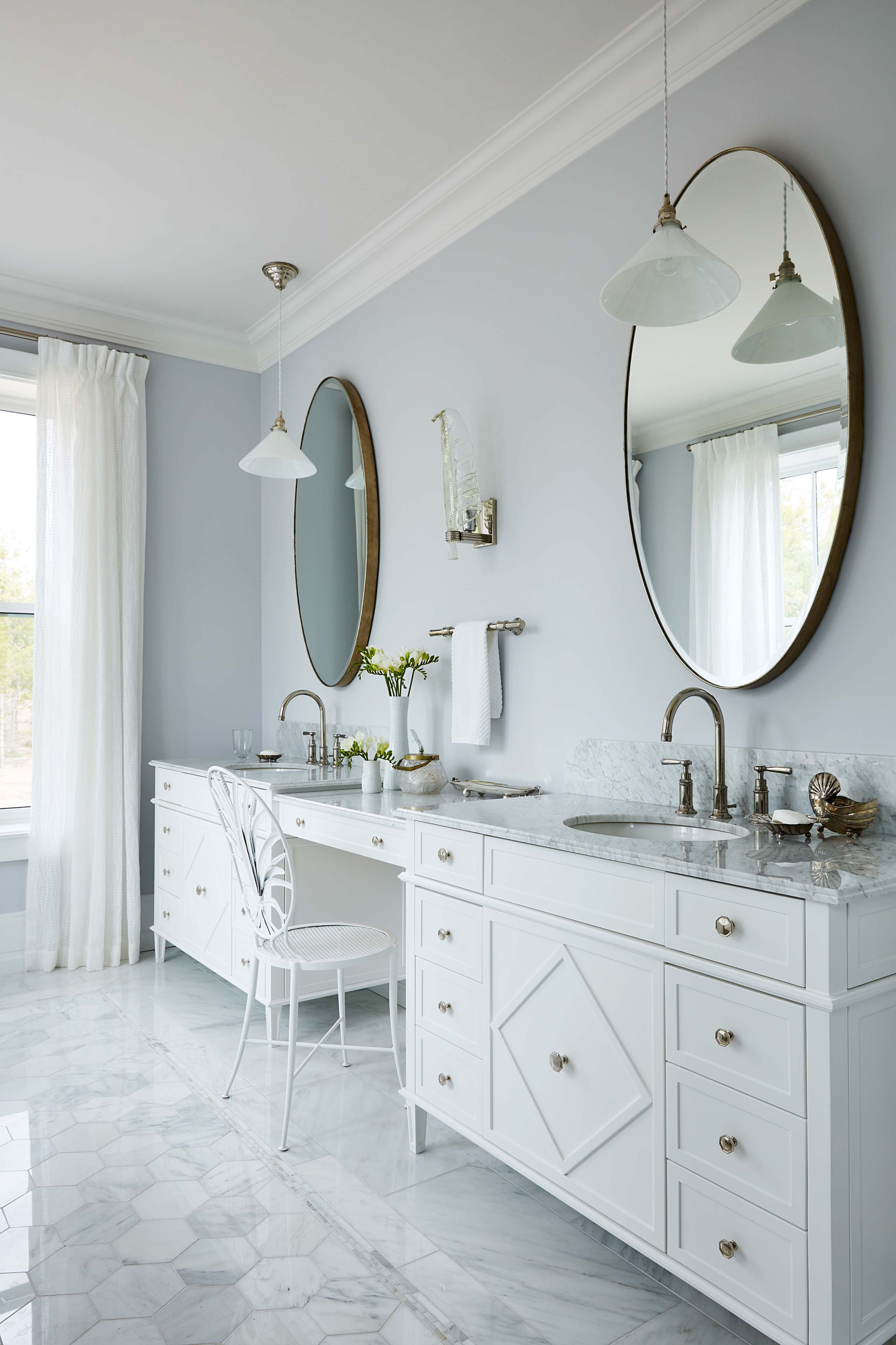 Elegant double vanities in serene marble bath with round mirrors and blue grey walls by Sarah Richardson