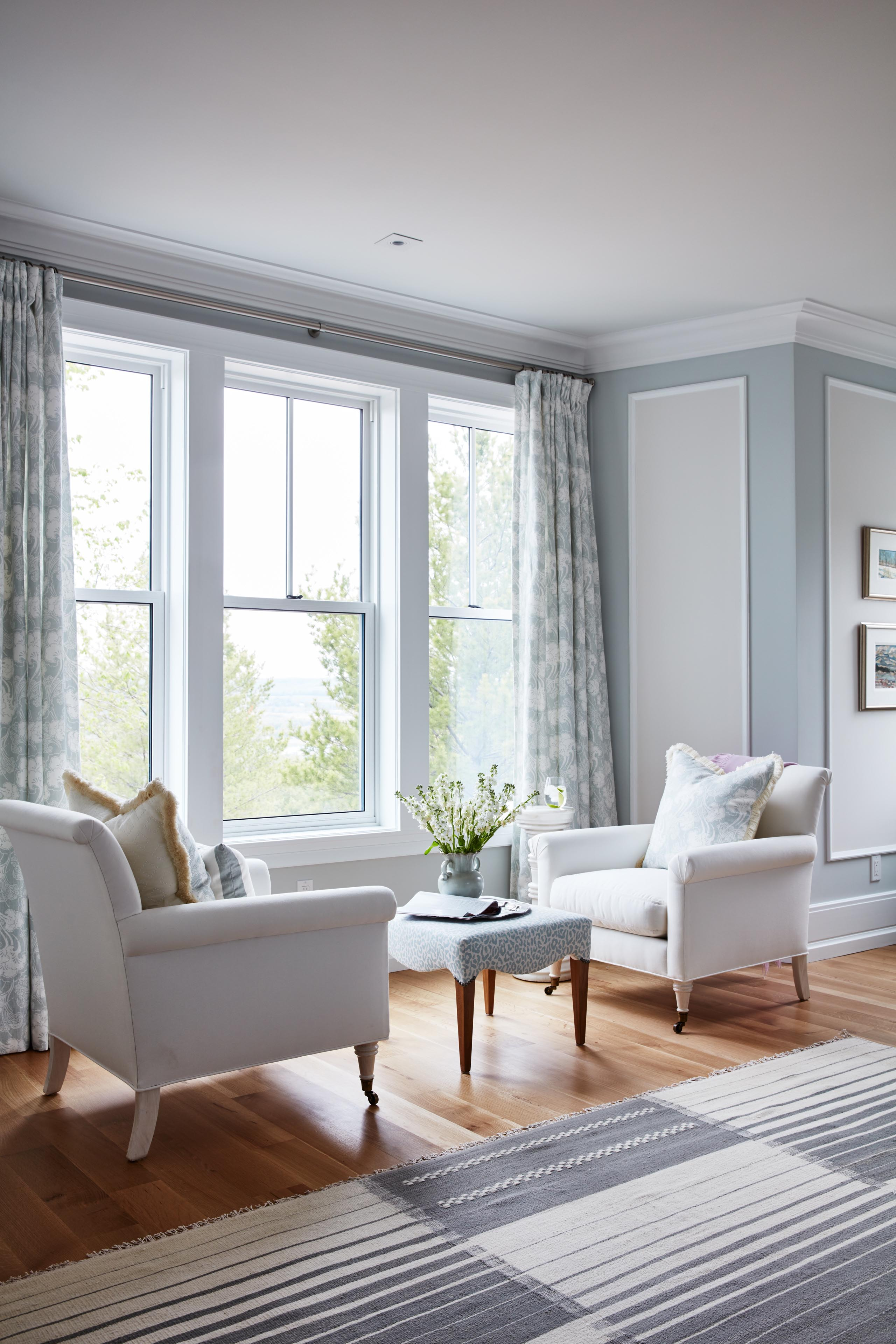 Beautiful seating area with armchairs in front of window in blue master bedroom designed by Sarah Richardson