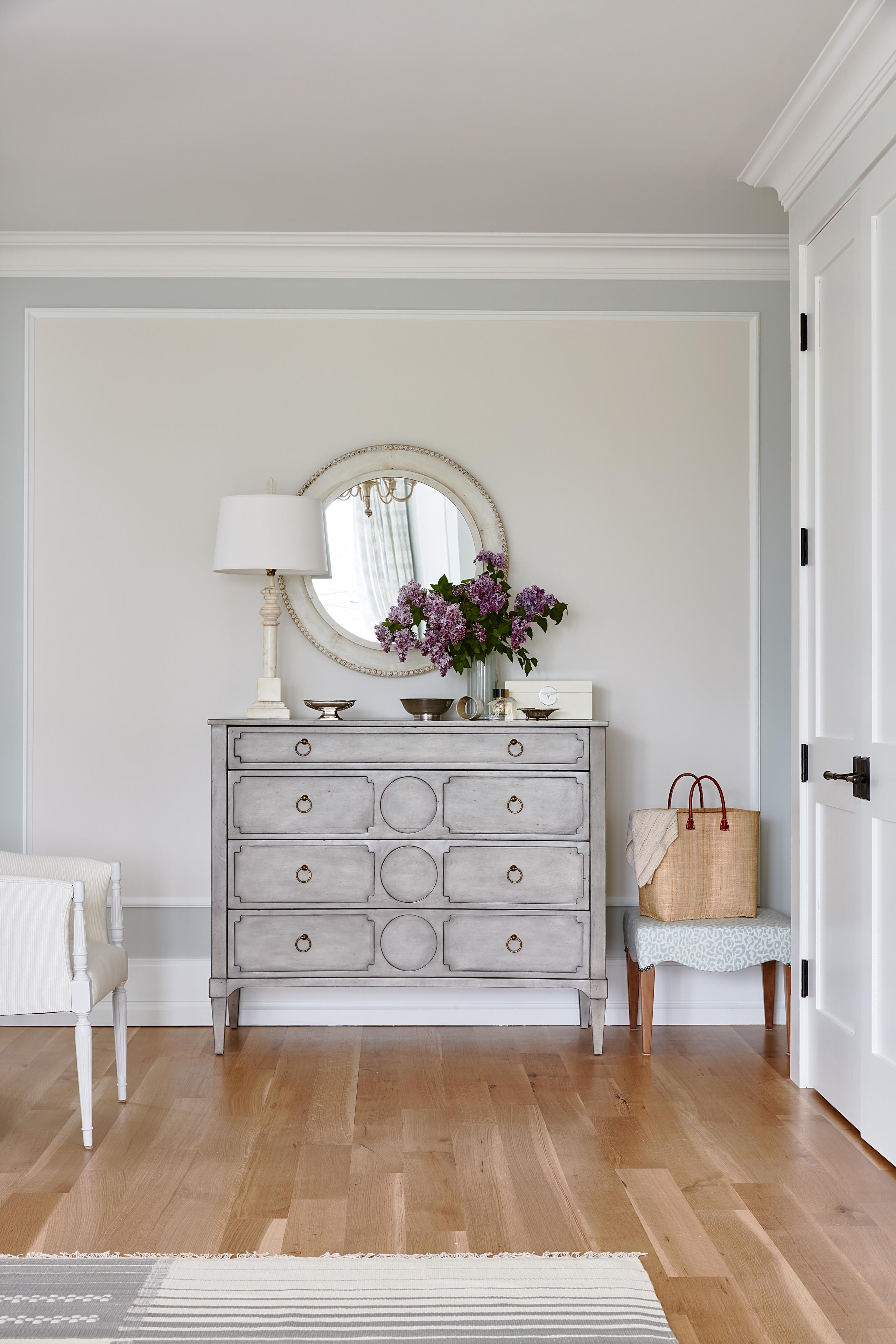 Elegant grey chest with round mirror in Sarah Richardson master bedroom with blue grey