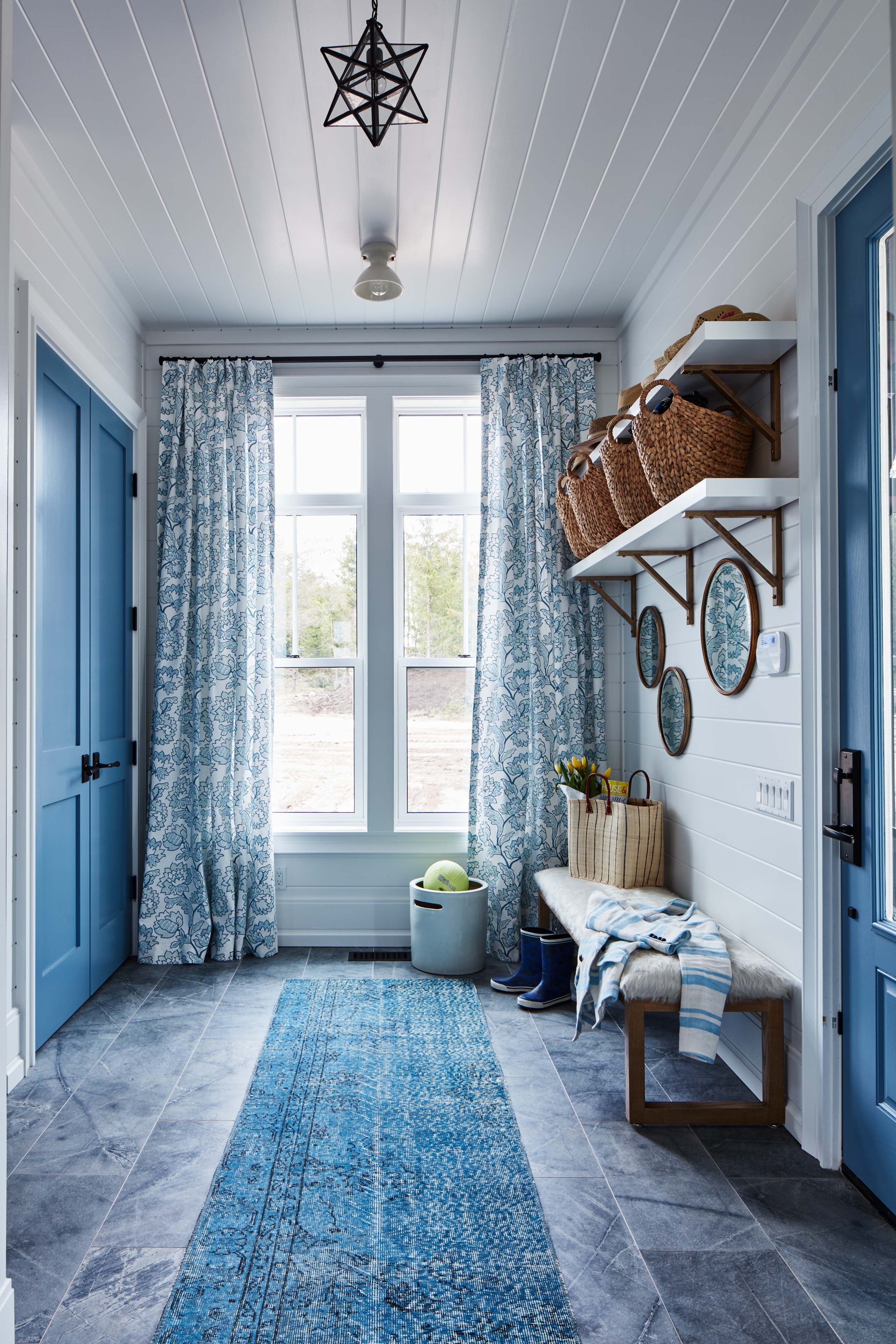 Soft blues distinguish this mud room with its elongated bench and easily washed tiles. #mudroom #blueandwhite #beadboardceiling #SarahRichardson