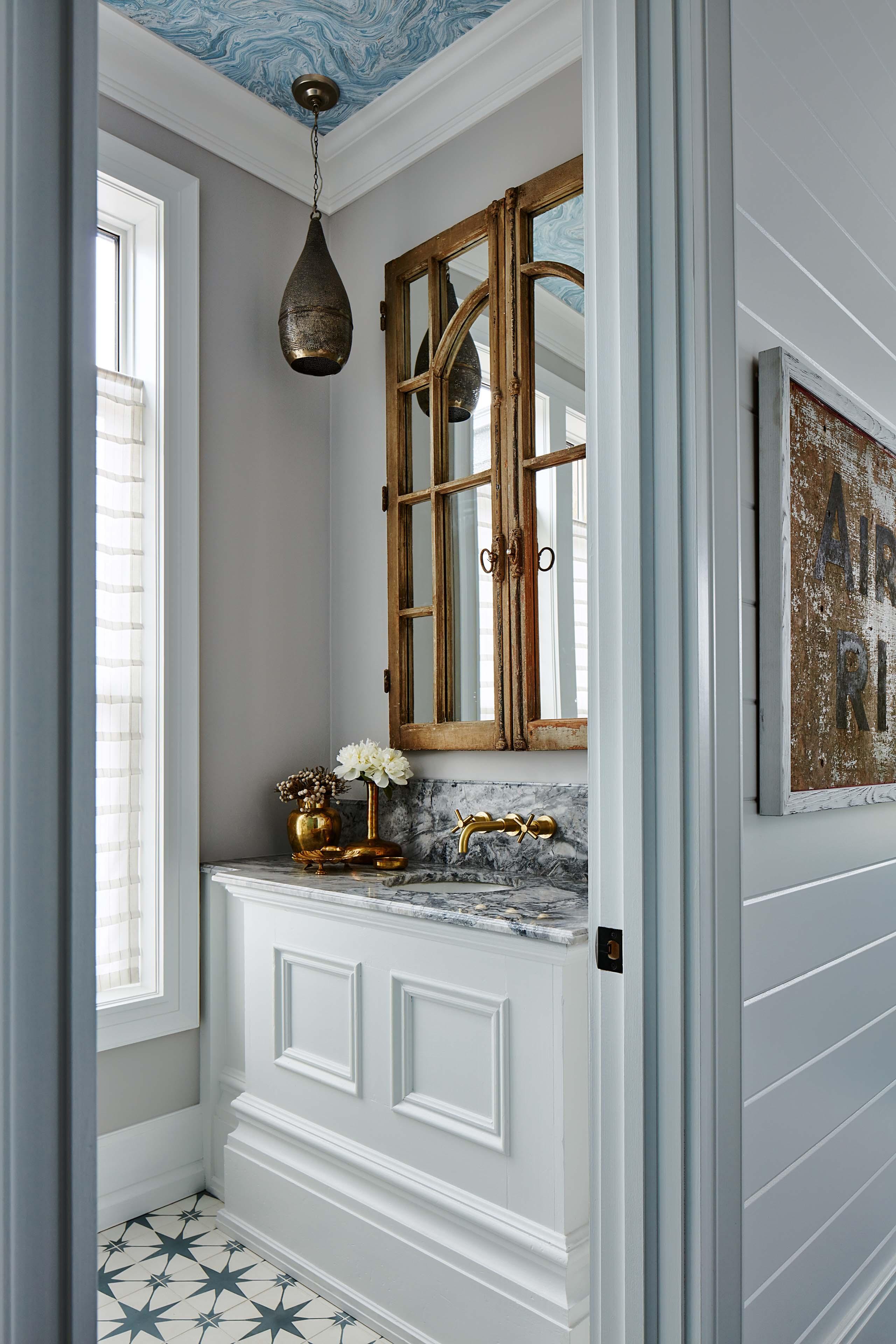A small powder room feels like a jewel box thanks to pretty star-inspired tiling. #SarahRichardson #powcerroom #blueandwhite #marbledesign