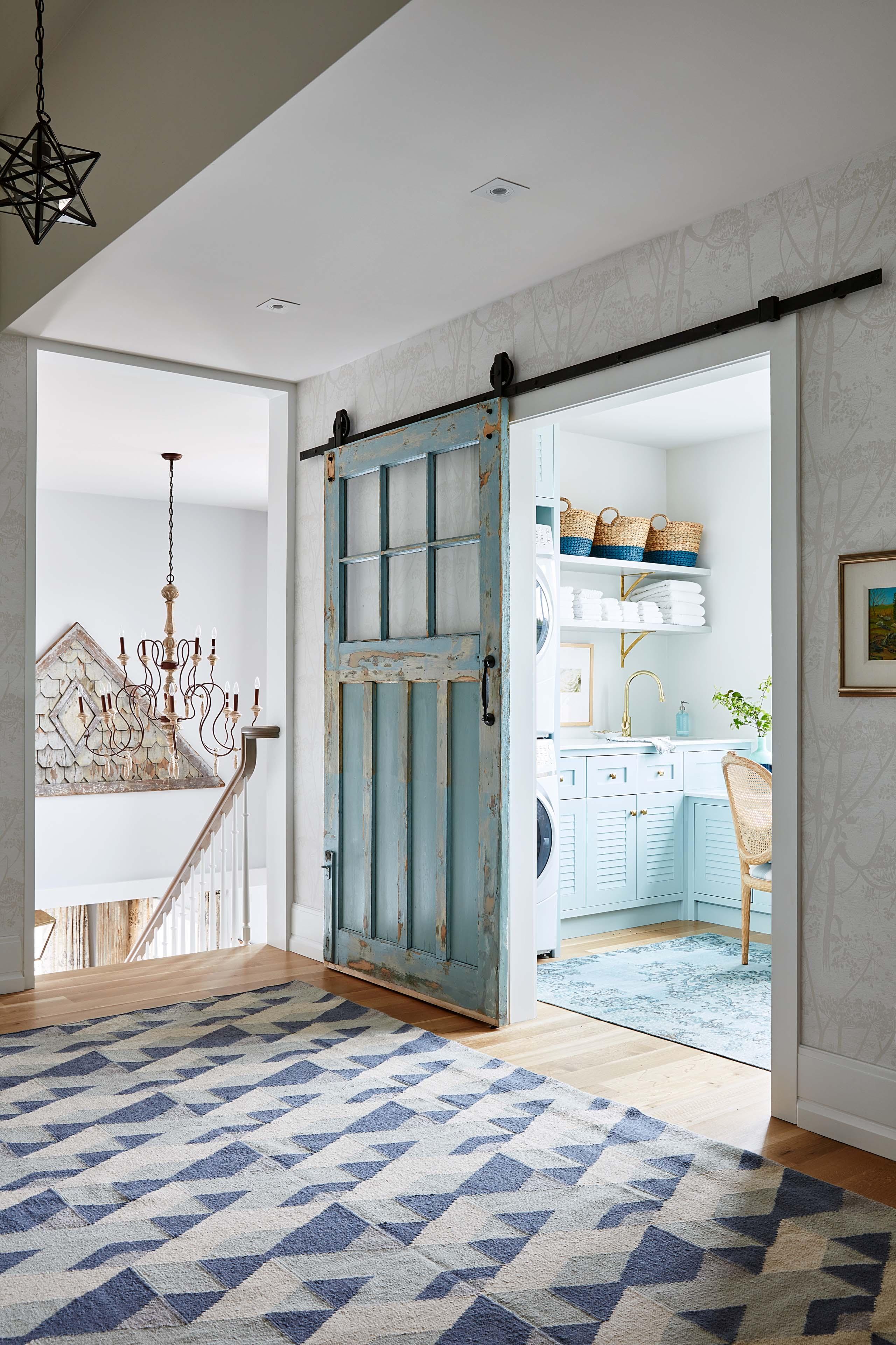 Sliding farmhouse door wih peely turquoise paint in classic home by #SarahRichardsn. #barndoor #turquoisedoor #farmhouselaundryroom
